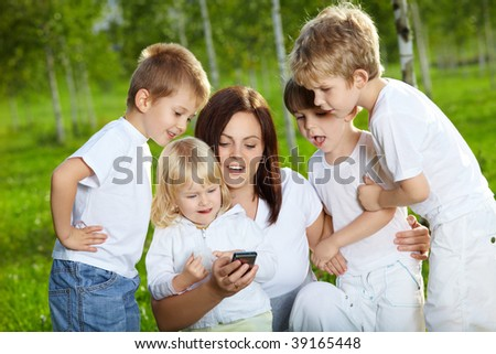 Four small child and mother are interested by a mobile phone in a summer garden - stock photo