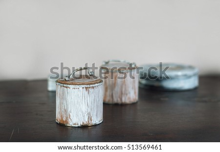 four small old boxes painted white on the wooden table