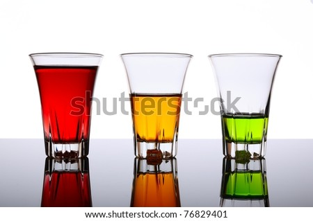 Four small shot glasses of alcoholic beverages - stock photo
