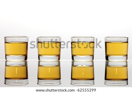 Four small shot glasses of whiskey - stock photo
