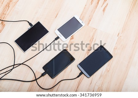 four smartphones connected to chargers - stock photo