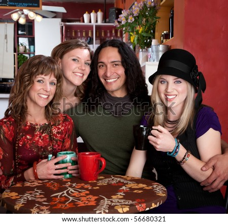 Four smiling friends enjoying coffee in a cafe - stock photo