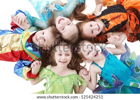 Four smiling girls and one boy lay head to head like petals of flower - stock photo