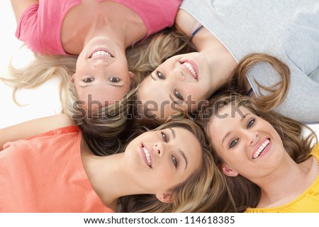 Four smiling girls lying on the ground together with their heads beside one another - stock photo