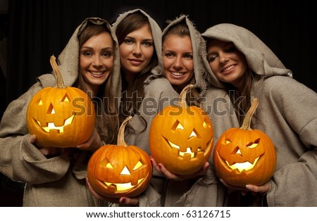 Four smiling nuns in cassocks holding halloween pumpkins - stock photo