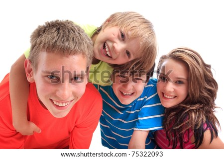Four smiling siblings, three boys and one girl,  isolated against a white background. - stock photo