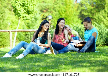four smiling student girls studying in green park - stock photo