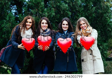 Four smiling women showing hearts - stock photo