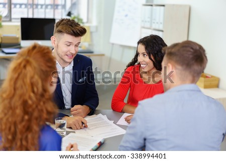 four smiling young businesspeople talking in a meeting - stock photo