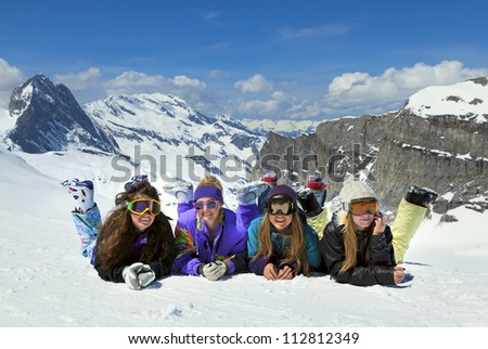 Four smiling young girls are snowboarders on the snow in mountains in French Alps - stock photo