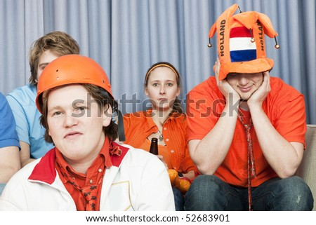 Four soccer fans, watching a game at home, in disbelief about the outcome of the game - stock photo