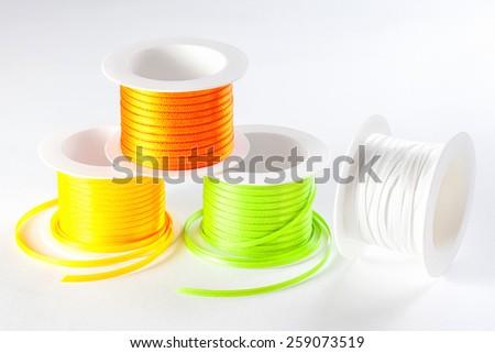 four spools of ribbon on white background - stock photo
