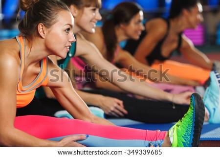 four sporty women stretching legs on the mats in the gym - stock photo