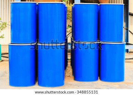 Four stack of blue barrels standing on a chemical plant - stock photo