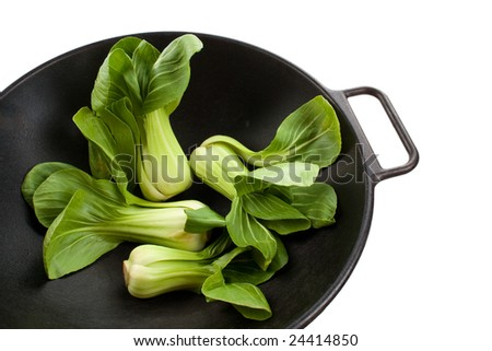 Four Stalks of baby bok choy in a black wok - stock photo