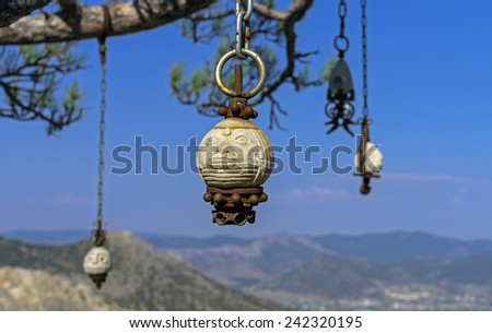 Four stone idol hanging on a pine tree in the Crimean mountains. Probably the temple of the followers of some new esoteric teaching. - stock photo
