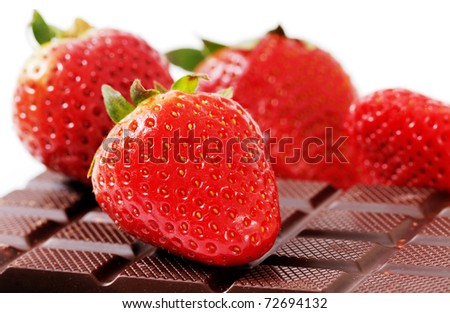 Four strawberries and black chocolate with nut. - stock photo