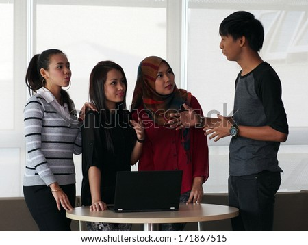 Four students in a discussion - stock photo