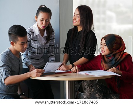 Four students in discussion - stock photo