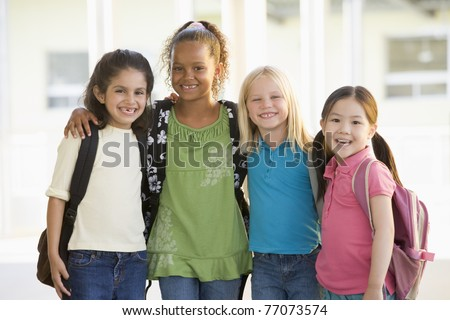 Four students outside school standing together smiling (high key) - stock photo