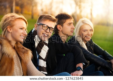Four students sitting in the park smiling and laughing - two couples - stock photo