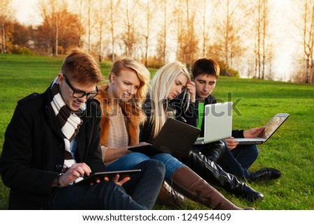 Four students, two couples working on laptops in the spring evening park - stock photo