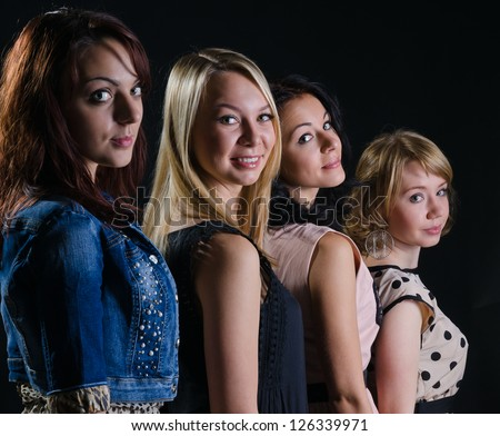 Four stylish beautiful women posing standing in a row looking back at the camera with charming smiles against a dark background - stock photo