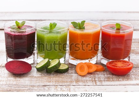 Four summer drink vegetable smoothies. Tomato, cucumber, carrot, beet Juices and vegetables on white wooden table - stock photo