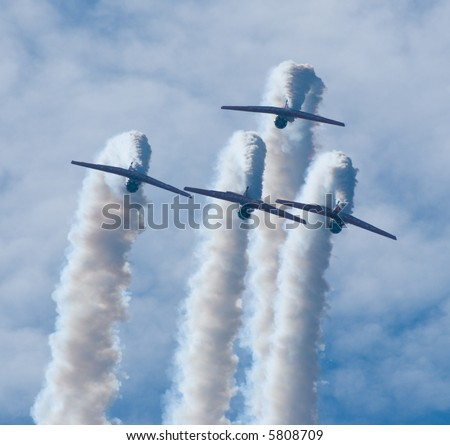 Four T-6 Texan SNJ WWII trainer airplanes performing a show - stock photo