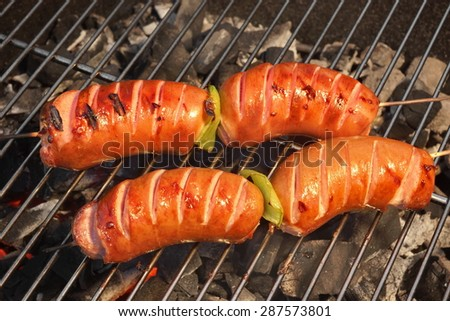 Four Tasty Sausages On The Hot Barbecue Charcoal Grill Close-up. Good Snack For Summer Outdoor BBQ Party Or Picnic - stock photo