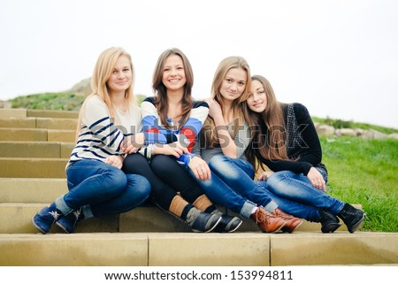Four teen girls friends having fun happy smiling & looking at camera on the green outdoors background - stock photo