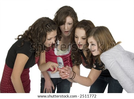four teen girls looking at cell phone - stock photo