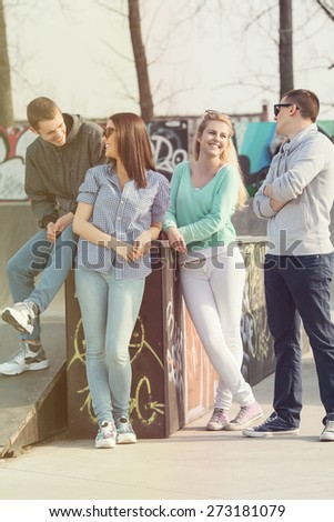 Four teenage friends hanging out in a skate park or schoolyard - stock photo
