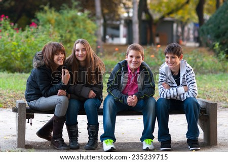 Four teenage friends having fun in the park on beautiful autumn day. - stock photo