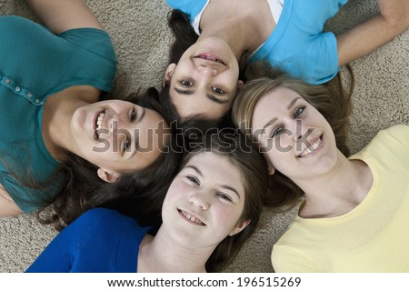 Four teenage girlfriends having fun while lying down head to head on a white carpeted floor - stock photo