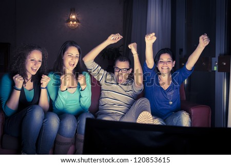 Four teenager in front of television - stock photo