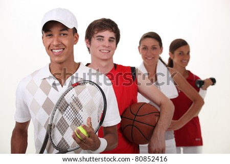 Four teenagers dressed for different sports - stock photo