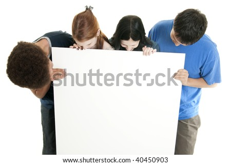 Four teenagers of various ethnic backgrounds holding and looking at a blank sign. - stock photo