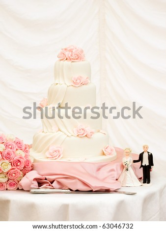 Four Tier Wedding Cake Decorated with Pink Roses - stock photo