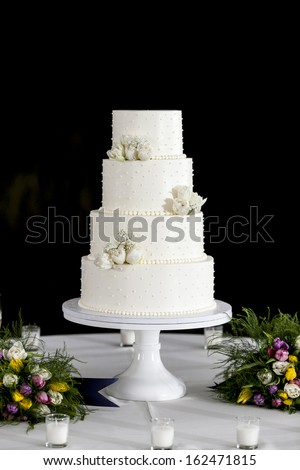 four tiered white wedding cake with black background - stock photo