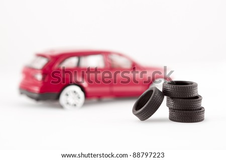 Four tires (from a toy car) stacked up and focused - the de-focused toy car (without tires) serves as a background. - stock photo