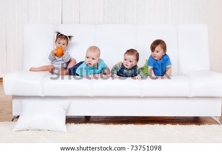 Four toddler friends on the sofa - stock photo