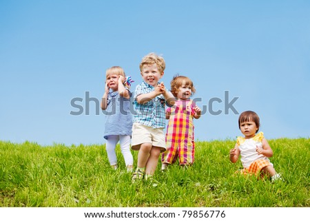 Four toddlers on the grass against blue sky - stock photo