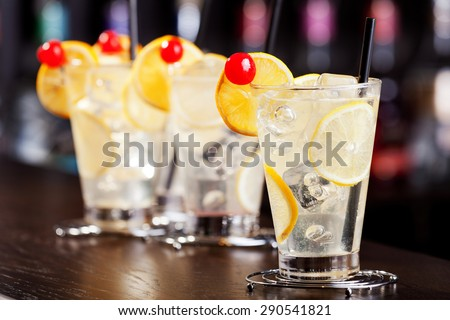 Four Tom Collins cocktails shot on a bar counter in a nightclub