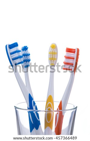 Four toothbrushes in a glass, isolated on white background, close-up.