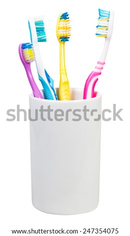 four toothbrushes in ceramic glass - family set of toothbrushes isolated on white background - stock photo