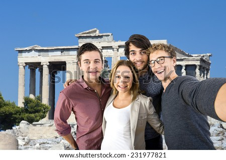 Four tourists taking a selfie in front of an old Greek temple during their vacation - stock photo