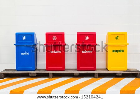 Four trash cans for collecting different type of waste with waste type label in Thai : general waste label on blue bin, hazardous waste label on red bins and municipal solid waste label on yellow bin - stock photo
