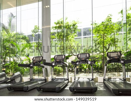 Four Treadmill in a gym with high ceiling in front of a big glass window - stock photo
