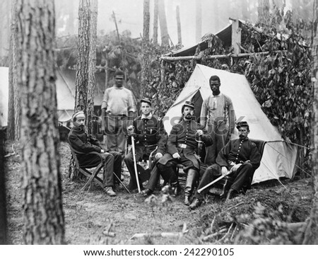 Four union officers in front of tent, with two Africans-American during the Petersburg Campaign. Many former slaves, emancipated in 1863, were employed a servants to Union officers. August, 1864. - stock photo